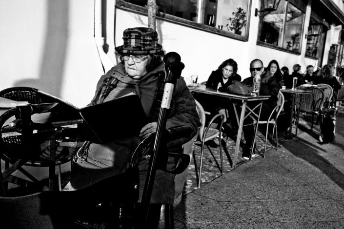 And older woman sitting reading a menu in Potsdam. Street Photography by Victor Borst