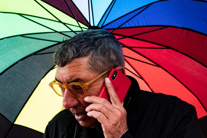Colorful rainbow umbrella with a man making a phone call. Street photography by Victor Borst